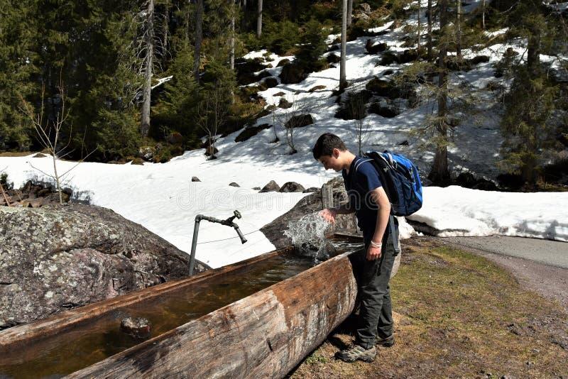 Niño jugando con el agua en un valle de agua de madera rodeado de nieve cerca de un camino turístico que se dirige directamente a fotos de archivo libres de regalías