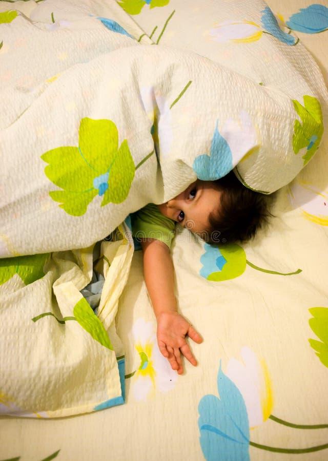 Niño juguetón en cama fotos de archivo libres de regalías