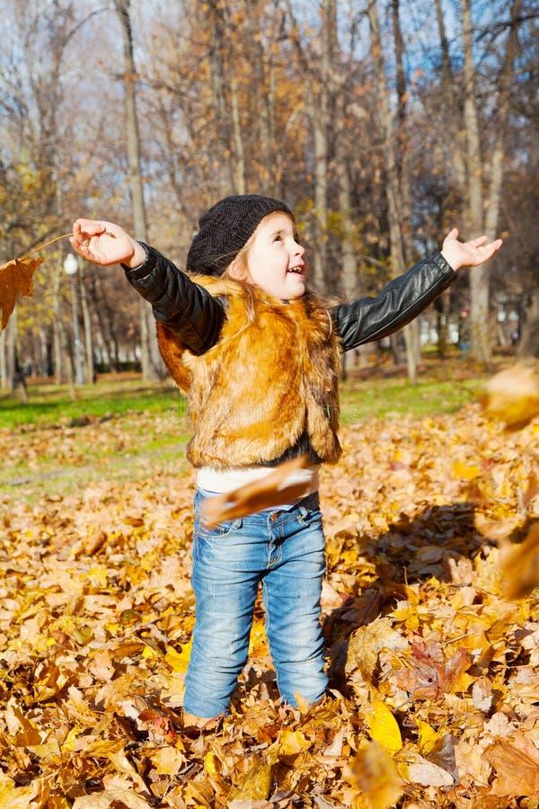 Niño la muchacha a colocarse en parque del otoño fotografía de archivo