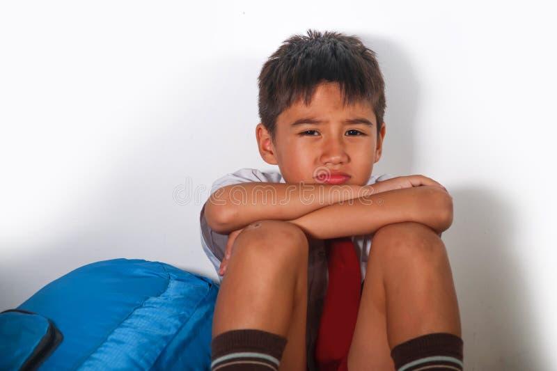 Niño latino asustado triste joven 8 años en el uniforme escolar y la mochila que se sientan abus sufridor solamente llorando pres fotos de archivo