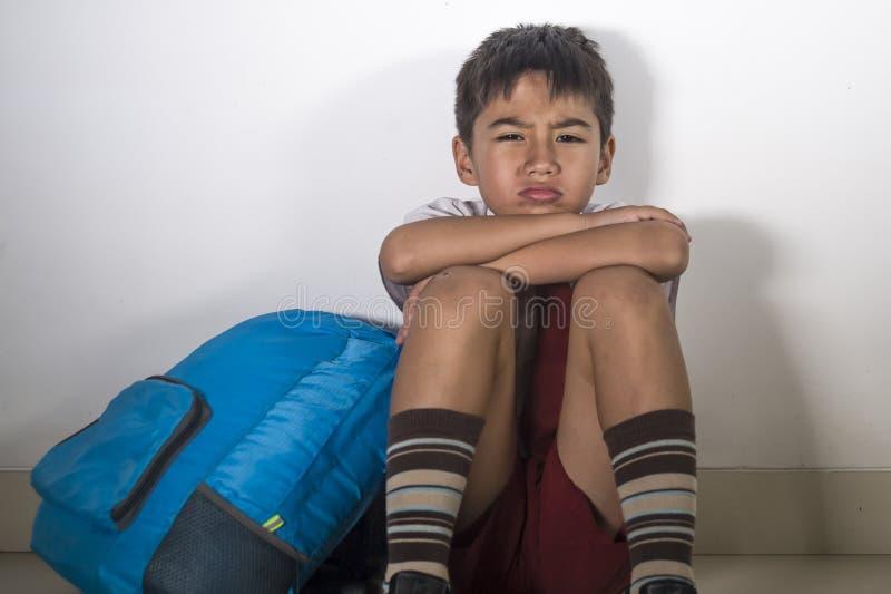 Niño latino asustado triste joven 8 años en el uniforme escolar y la mochila que se sientan abus sufridor solamente llorando pres fotografía de archivo