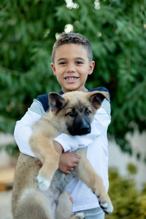 Niño latino con su perro imagen de archivo