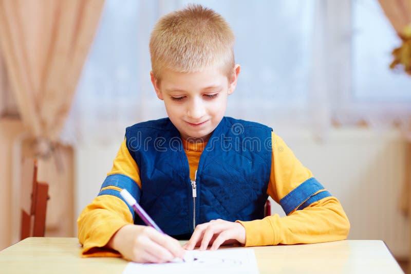 Niño lindo con la necesidad especial que se sienta en el escritorio, escribiendo en cuaderno en sala de clase imágenes de archivo libres de regalías