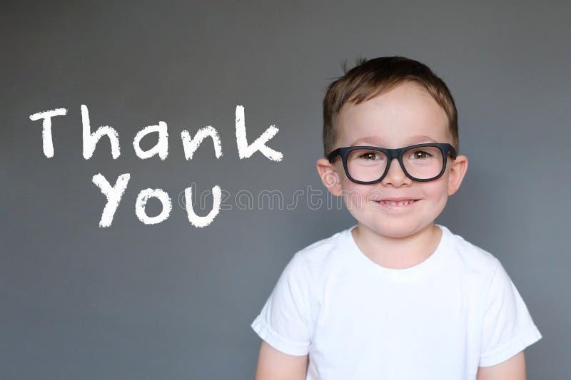 Niño lindo con un agradecimiento usted mensaje foto de archivo libre de regalías