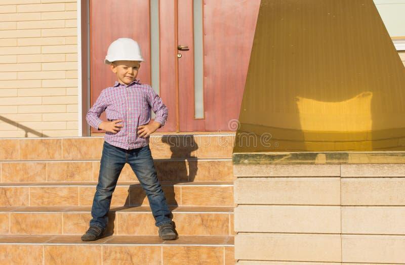 Niño lindo en el casco que presenta en las escaleras fotografía de archivo libre de regalías
