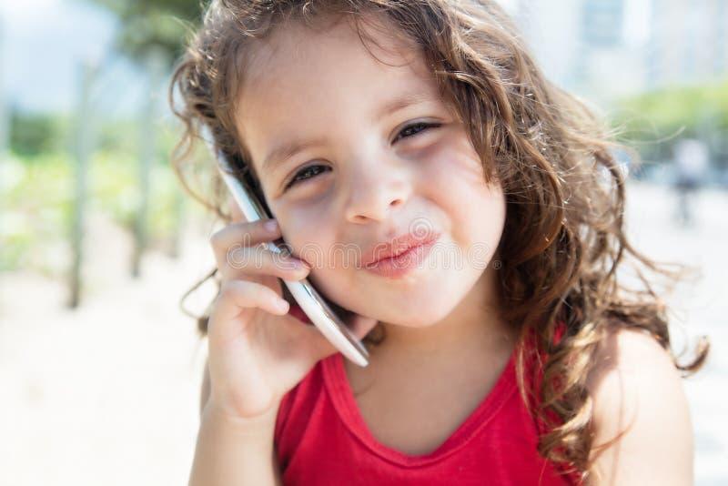 Niño lindo en una camisa roja que escucha en el teléfono móvil afuera foto de archivo