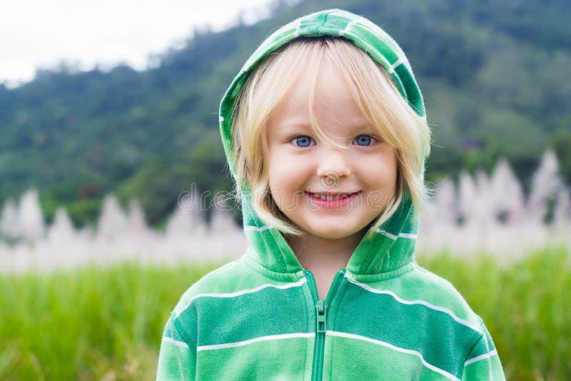 Niño lindo, feliz en sudadera con capucha delante de un campo fotografía de archivo