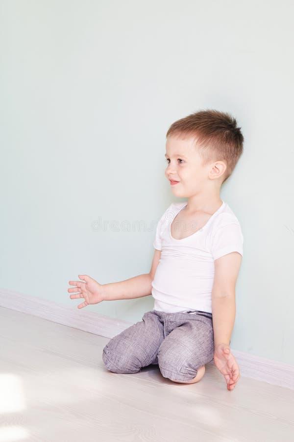 Niño lindo feliz que alcanza hacia fuera sus palmas y que coge algo imagenes de archivo