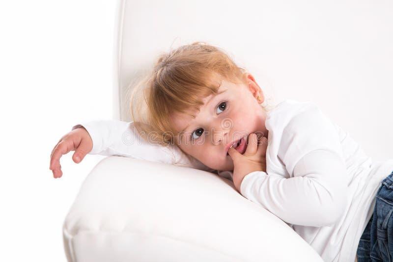 Niño lindo - muchacha tímida que miente en el sofá blanco que chupa el pulgar o el finge imágenes de archivo libres de regalías