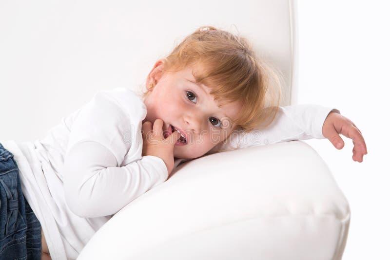 Niño lindo - muchacha tímida que miente en el sofá blanco que chupa el pulgar o el finge fotografía de archivo libre de regalías