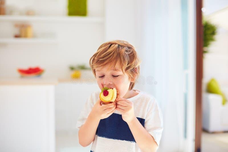 Niño lindo, muchacho joven comiendo la magdalena sabrosa con crema y frutas azotadas en casa foto de archivo