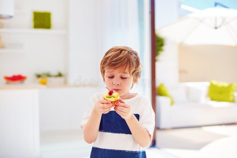 Niño lindo, muchacho joven comiendo la magdalena sabrosa con crema y frutas azotadas en casa imagen de archivo libre de regalías