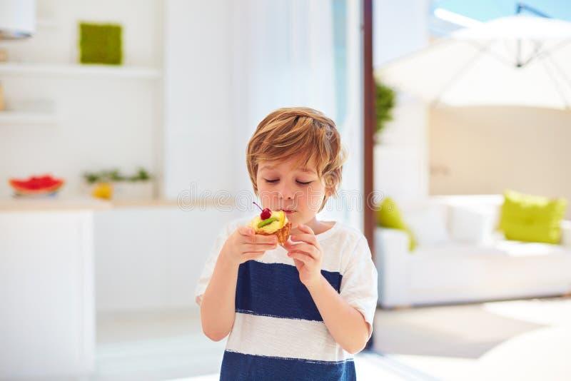 Niño lindo, muchacho joven comiendo la magdalena sabrosa con crema y frutas azotadas en casa imagen de archivo