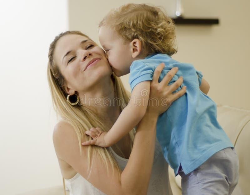 Niño lindo que besa a su mamá imágenes de archivo libres de regalías