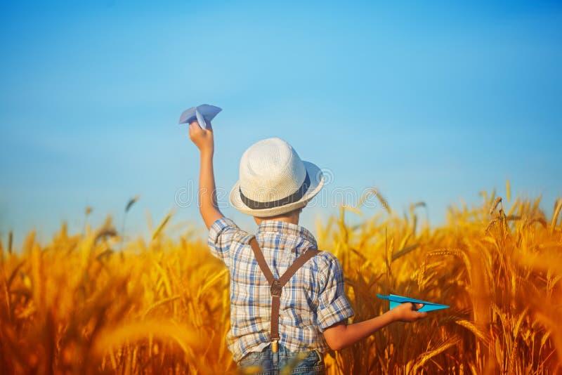 Niño lindo que camina en el campo de oro del trigo en un verano soleado d imagen de archivo
