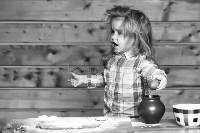 Niño lindo que cocina con pasta, harina, el huevo y el cuenco imágenes de archivo libres de regalías