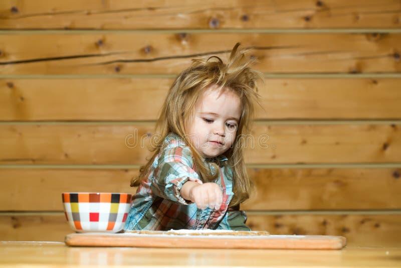 Niño lindo que cocina con pasta, harina y el cuenco en la madera fotos de archivo libres de regalías