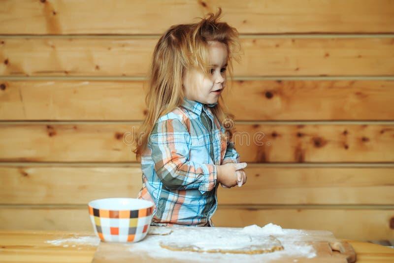 Niño lindo que cocina con pasta, harina y el cuenco en la madera foto de archivo libre de regalías