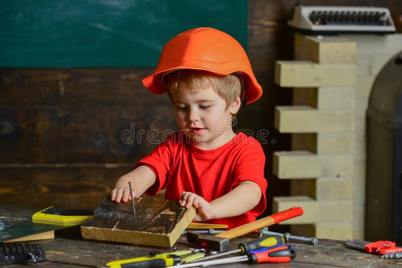 Niño lindo que juega con el sistema de herramienta Pequeño carpintero que trabaja con el bloque de madera Pequeño muchacho en tal imagen de archivo libre de regalías