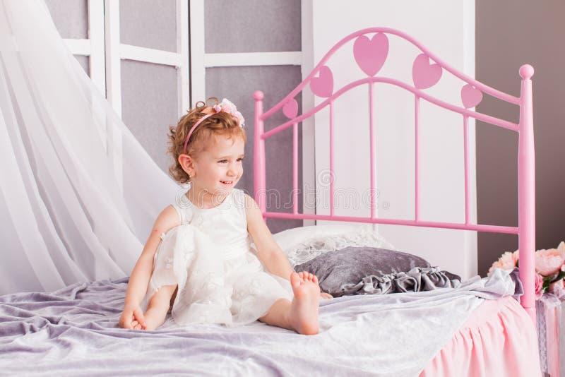Niño lindo que se sienta en su cama que lleva una venda fotos de archivo libres de regalías
