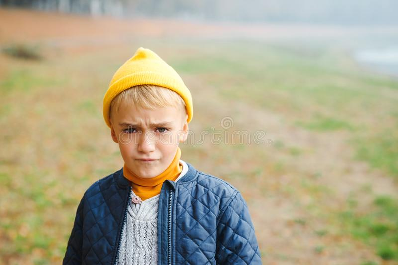Niño lindo trastornado que mira la cámara, retrato del aire libre Muchacho hermoso del niño que tiene mirada escéptica y desconte foto de archivo