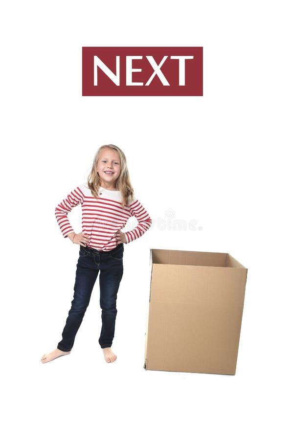Niño lindo y dulce del pelo rubio que se coloca al lado de la caja de cartón que aprende el sistema de tarjeta inglés imagenes de archivo