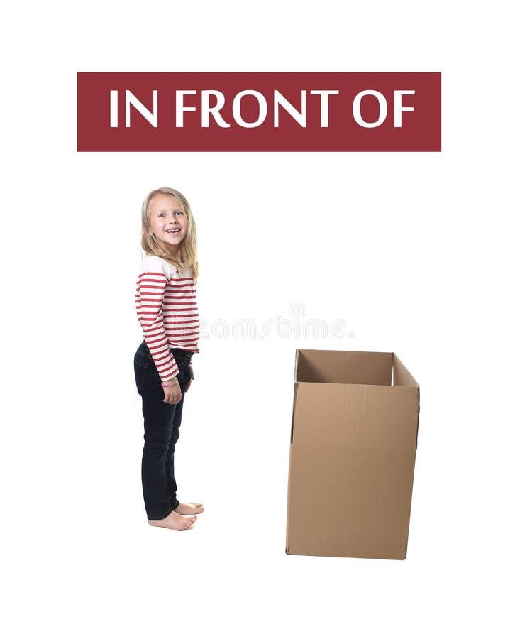 Niño lindo y dulce del pelo rubio que se coloca delante de la caja de cartón que aprende el sistema de tarjeta inglés fotos de archivo