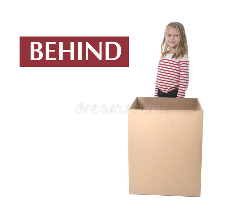 Niño lindo y dulce del pelo rubio que se coloca detrás de la caja de cartón que aprende el sistema de tarjeta inglés foto de archivo