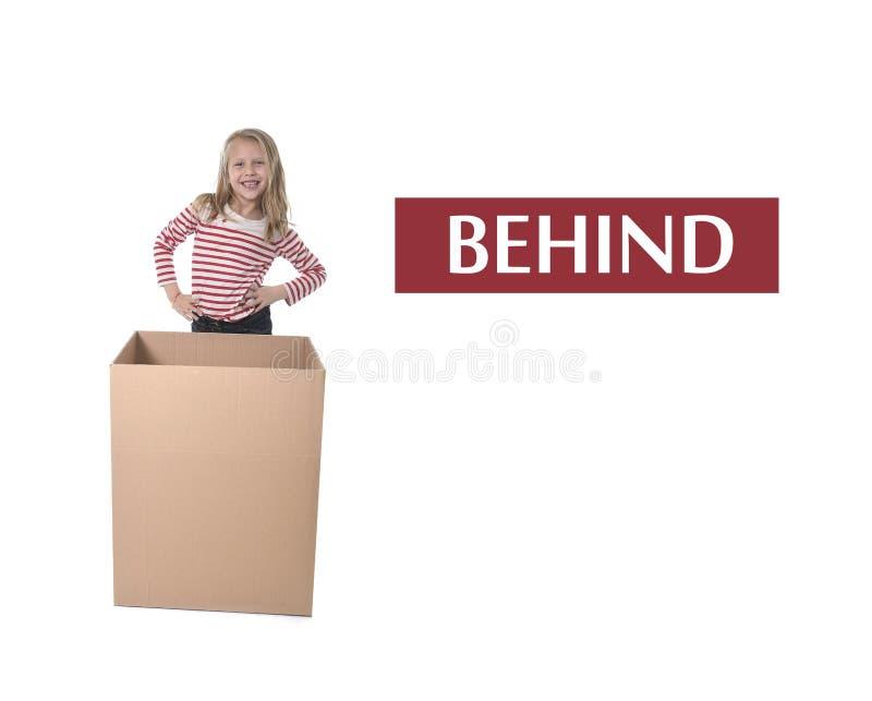 Niño lindo y dulce del pelo rubio que se coloca detrás de la caja de cartón que aprende el sistema de tarjeta inglés fotografía de archivo