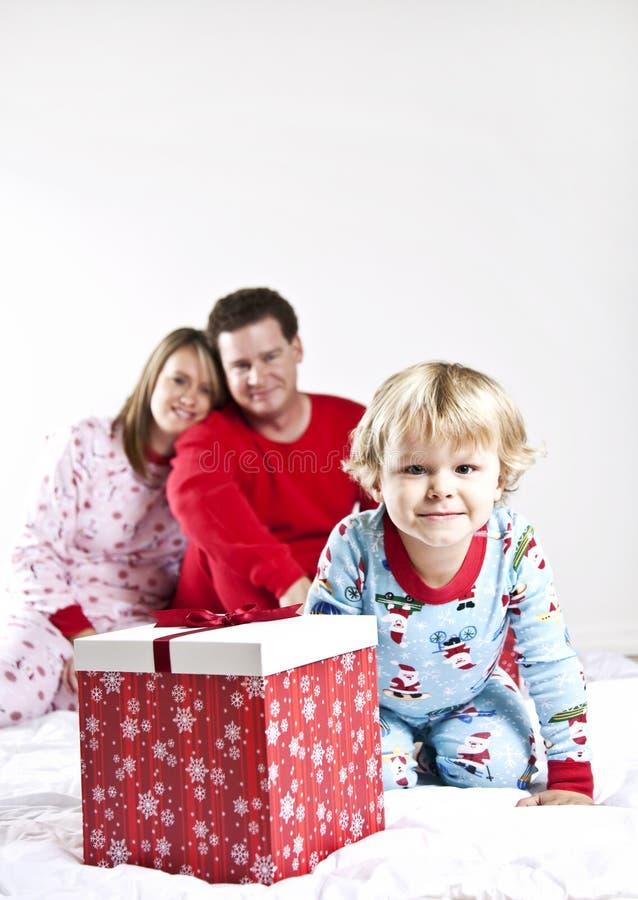 Niño listo para abrir los regalos el mañana de la Navidad foto de archivo
