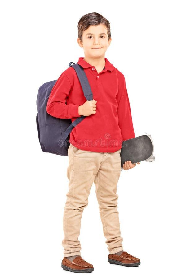 Niño masculino con la mochila y el monopatín aislados en el backgrou blanco fotografía de archivo libre de regalías