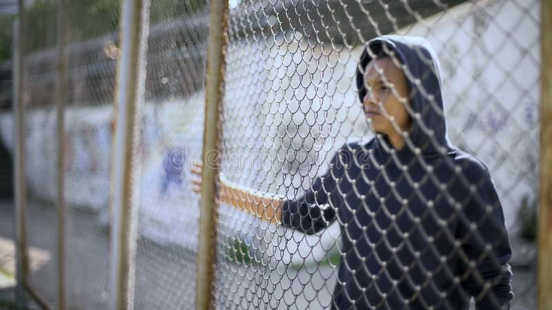 Niño migratorio separado de la familia, muchacho afroamericano detrás de la cerca, detenida imágenes de archivo libres de regalías