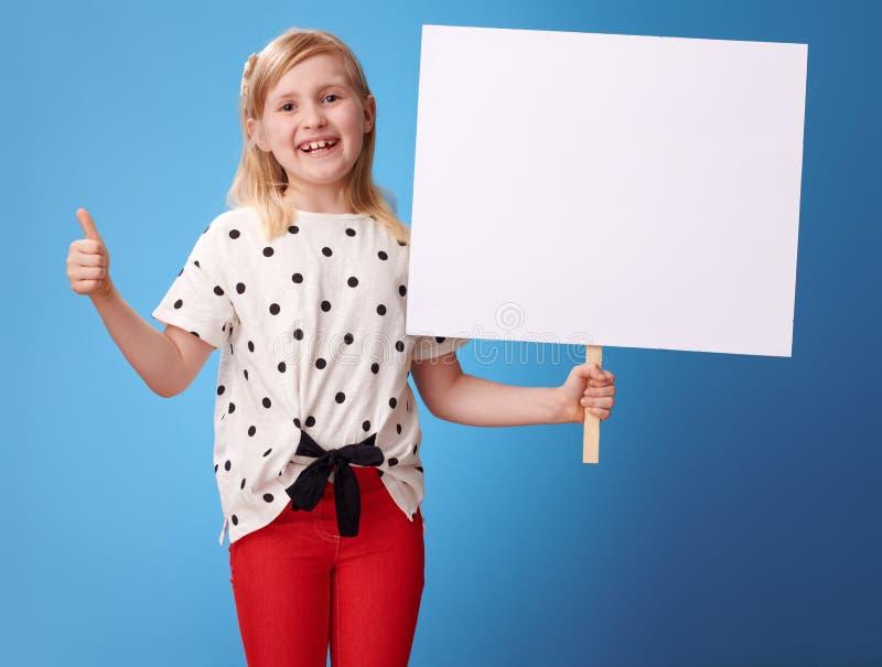 Niño moderno feliz que muestra el cartel y los pulgares en blanco para arriba en azul foto de archivo libre de regalías