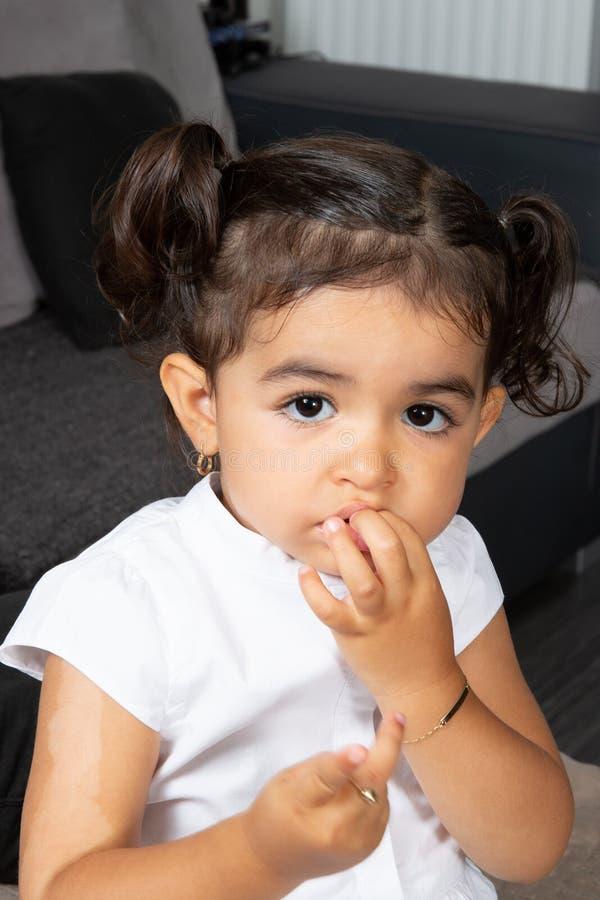 Niño moreno hermoso de la niña que se sienta en hacer de la sala de estar tímido con la mano en boca fotografía de archivo libre de regalías