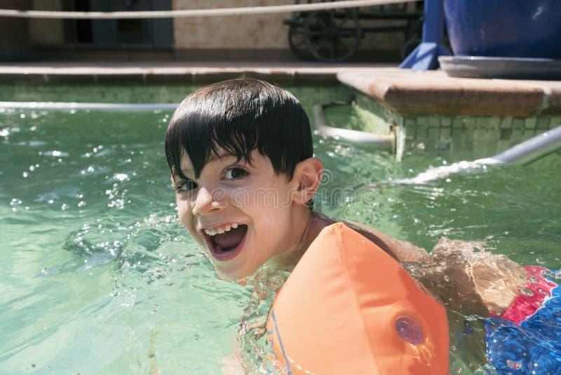 Niño moreno sonriente con risas de los flotadores del brazo imágenes de archivo libres de regalías