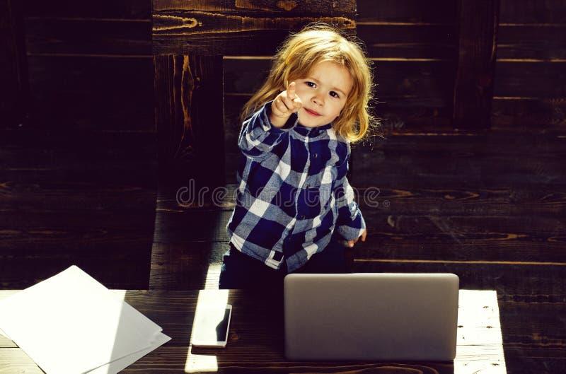Niño, muchacho de la pequeña empresa con el teléfono y ordenador en oficina fotos de archivo