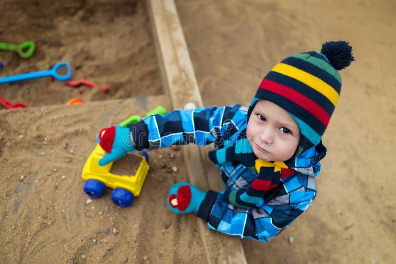 Niño muy serio que juega con los juguetes en la salvadera fotos de archivo libres de regalías