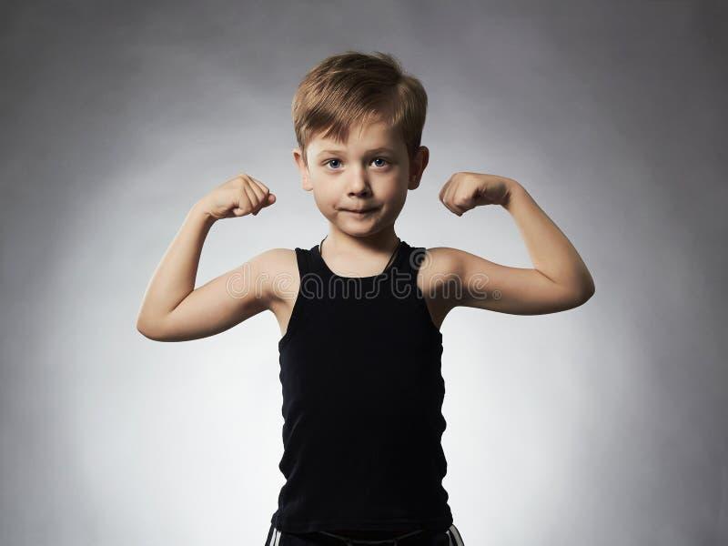 Niño Niño pequeño divertido Diviértase al muchacho hermoso que muestra sus músculos del bíceps de la mano foto de archivo