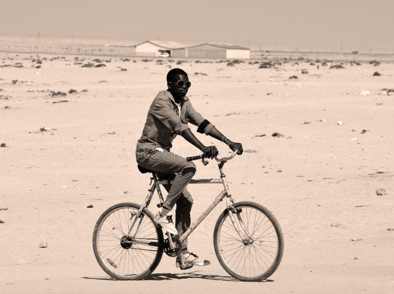 Niño no identificado biking en los tugurios de Mondesa fotos de archivo libres de regalías