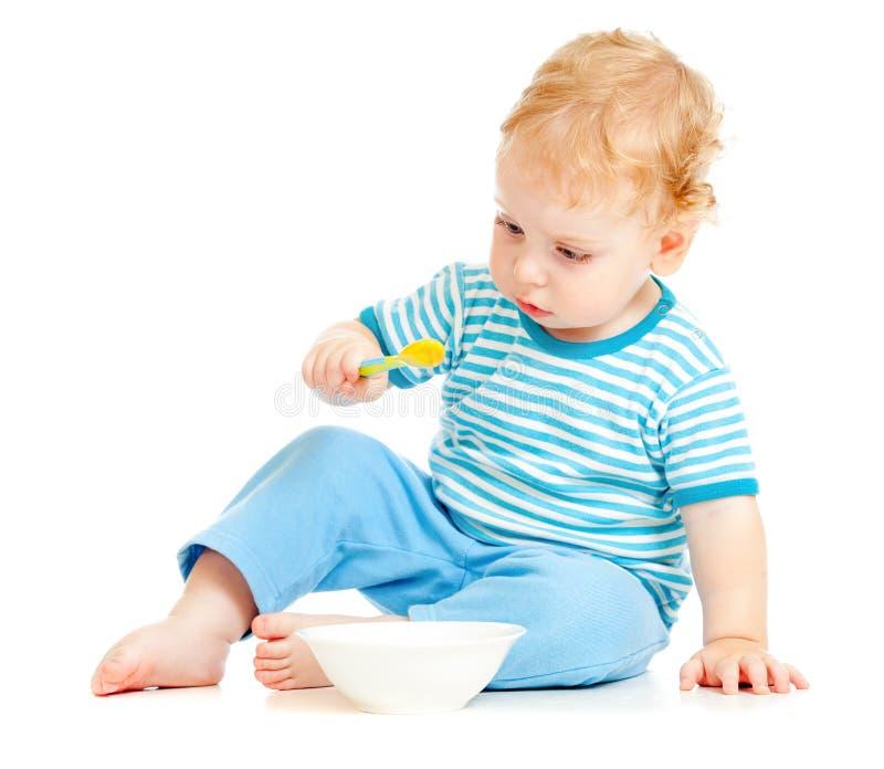 Niño o cabrito que come de la placa con la cuchara fotos de archivo