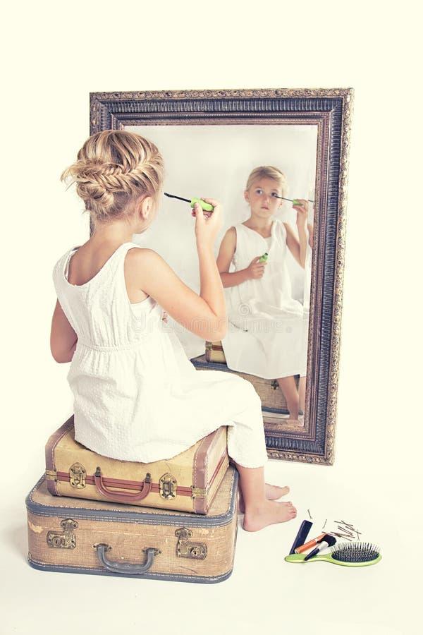 Niño o chica joven que pone en maquillaje mientras que mira se fotografía de archivo libre de regalías