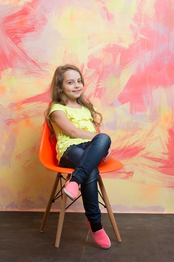 Niño o pequeña muchacha sonriente que se sienta en silla anaranjada imágenes de archivo libres de regalías