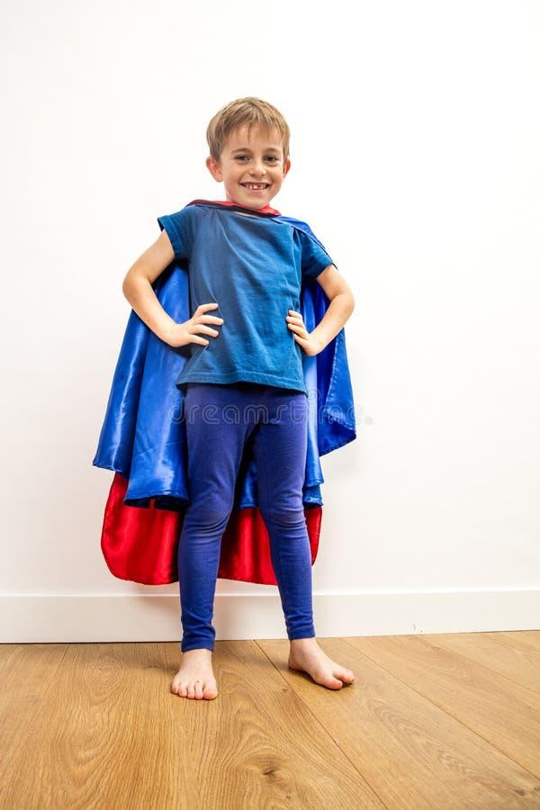 Niño orgulloso del superhéroe que mira fijamente para el poder y el lenguaje corporal fotografía de archivo libre de regalías