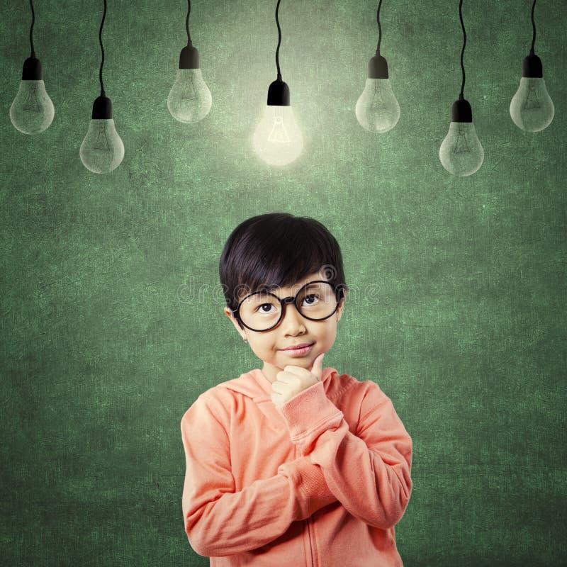 Niño pensativo con ropa casual debajo de la bombilla imagen de archivo