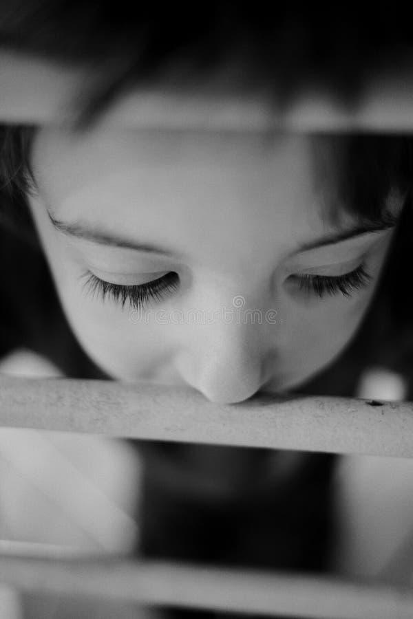 Niño pensativo que mira a través de la verja imagen de archivo libre de regalías