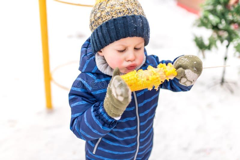 Niño pequeño 4-5 años, en invierno en ciudad en aire fresco en el fondo de la nieve El soplar en maíz hervido caliente Desayuno imagen de archivo