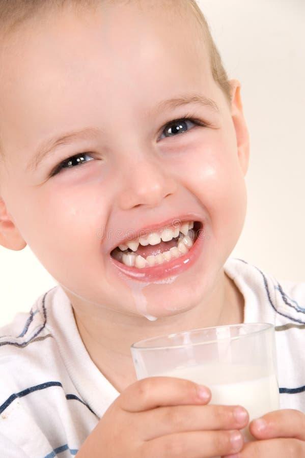 Niño pequeño adorable con el vidrio de leche foto de archivo