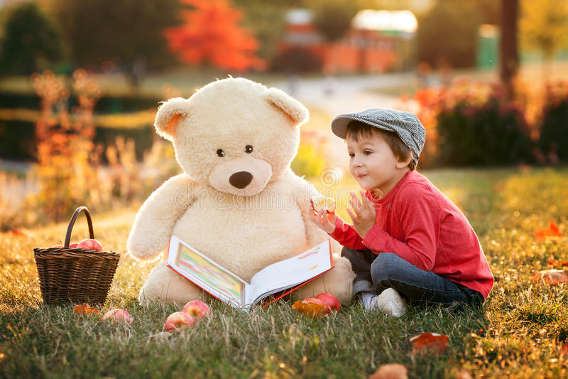 Niño pequeño adorable con su amigo del oso de peluche en el parque en su fotografía de archivo libre de regalías