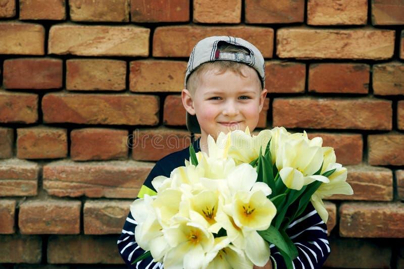 Niño pequeño adorable con un ramo de tulipanes fotos de archivo libres de regalías
