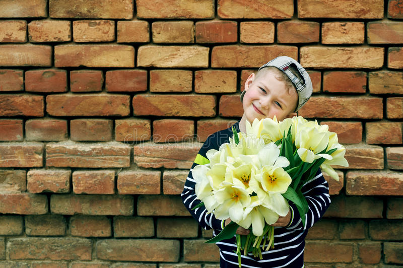Niño pequeño adorable con un ramo de tulipanes imagenes de archivo